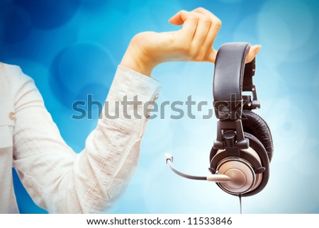 Women hand with headphone. Hand holding headphone. Dj, party, music studio, records, label. Some producer. Abstract background. Finger closeup.