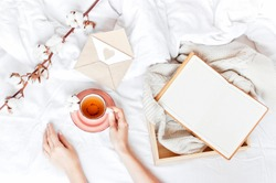 Women hands hold cup of hot tea with delicate cotton flower open notebook love letter tray white knitted sweater in the bed. Cozy morning breakfast at home. Lifestyle Copy Space autumn winter concept