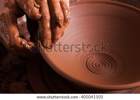Women hands. Potter at work. Creating dishes. Potter's wheel. Dirty hands in the clay and the potter's wheel with the product. Creation. Working potter.