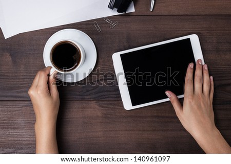 women hands with tablet computer and coffee on the table
