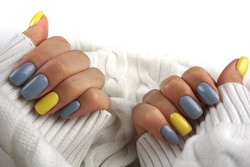 Women hands with Yellow and gray manicure. Trendy colours.