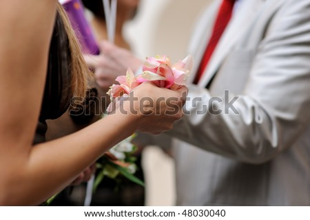 Women hang holding rose petals ready to throw - stock photo