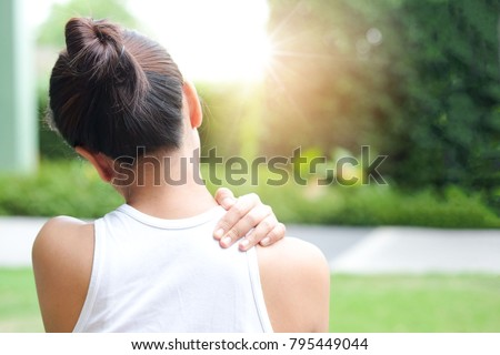 Women have neck pain, shoulder pain, at the park health concept. #795449044