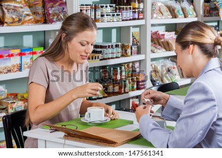 Women having coffee at table in grocery store