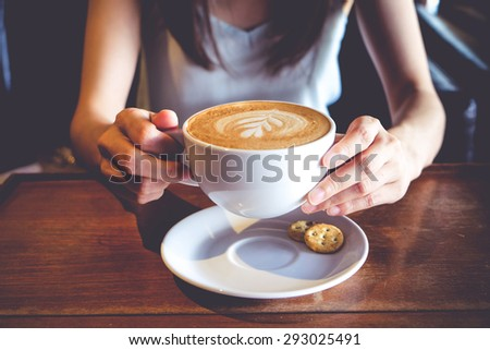 women hold a cup of latte art coffee on wood table, latte art