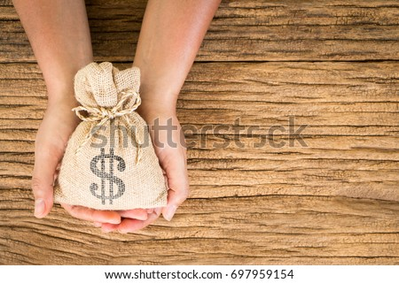 women hold a money bag on the...