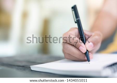 Women holding a pen writing a notebook. Recording concept