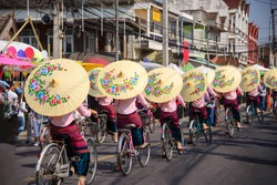 Women holding beautiful umbrellas and cycling. show at Bosang umbrella festival Chiang Mai, Thailand....