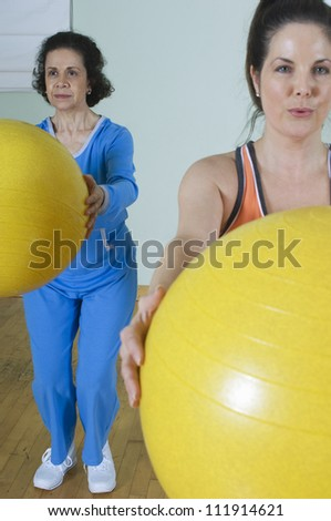 Women holding exercise balls in fitness class