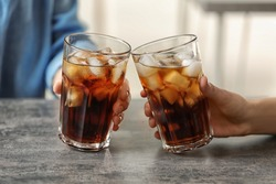 Women holding glasses of cola with ice at table, closeup