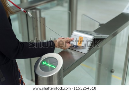 women holding key card access control to unlock security at an entrance gate