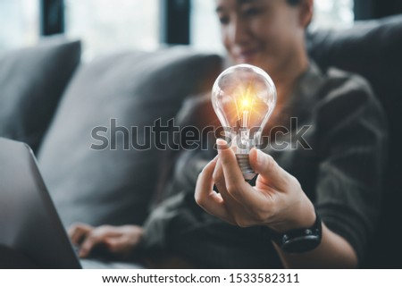 women holding light bulbs, ideas of new ideas with innovative technology and creativity.