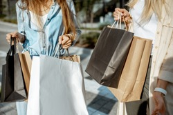Women holding shopping bags outdoors while shopping, close-up view on the empty paper bags with copy space