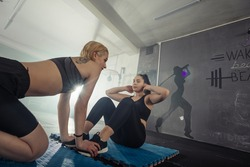 Women in black and white sportswear on a real group body Combat workout in the gym train to fight, kickboxing with a trainer.