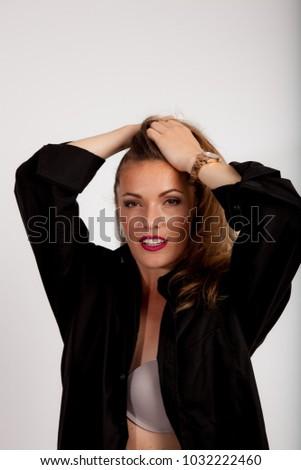 women in black shirt and grey bra doing her hair studio portrait on white background #1032222460