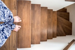Women in casual wearing walks down the stair in her home.