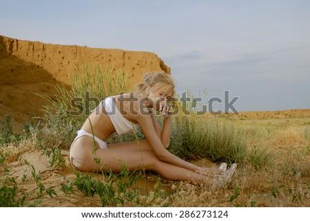 Women in desert. Female siting on desert sand