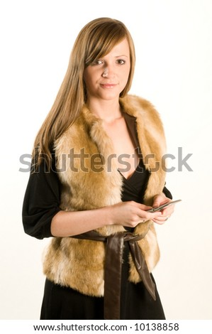 Women in fur vest with cell phone on white