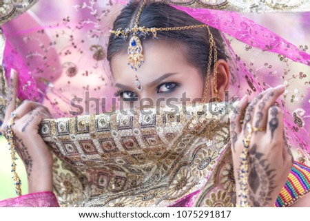 Women in Indian costumes cloak faces. #1075291817