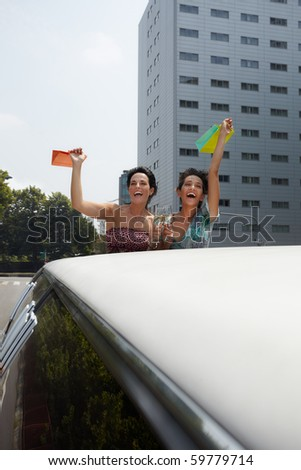 women in limousine toasting with champagne and showing shopping bags. Vertical shape, copy space