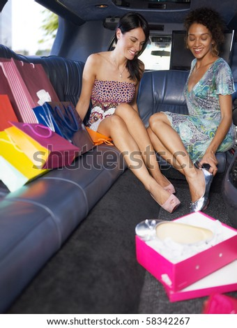 women in limousine trying on new shoes. Vertical shape, full length, copy space