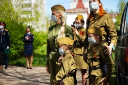 women in military uniforms and medical masks on their faces at a patriotic holiday. historical military festival during the coronavirus epidemic. soldiers on the street observe social distance