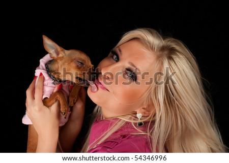 Women in pink  kiss little dog, dog licks face