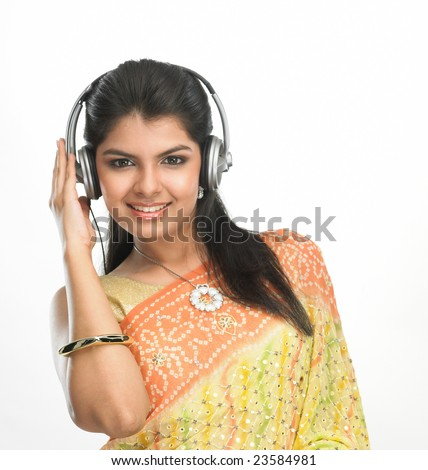 Women in sari hearing to music with head phones