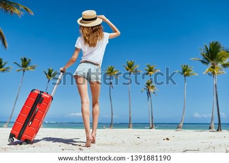 Women in short shorts in a T-shirt and in a straw hat walk along the sand on an island with palm trees from below                #1391881190