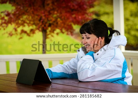 Women in the late twenties sitting with a tablet in the wooden arbor during the rainy autumn day