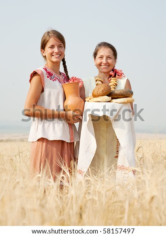 Women in traditional clothes with bread at cereals field