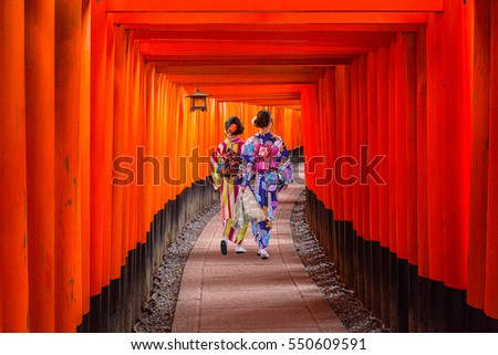 Photo of Women in traditional japanese kimonos walking at Fushimi Inari Shrine in Kyoto, Japan