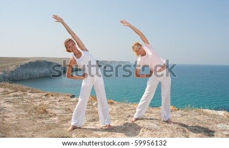 Women in white cloth practices Yoga in mountains against the sea
