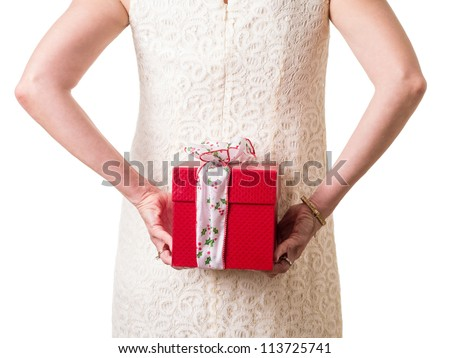 Women in white hiding a Christmas present behind her back.