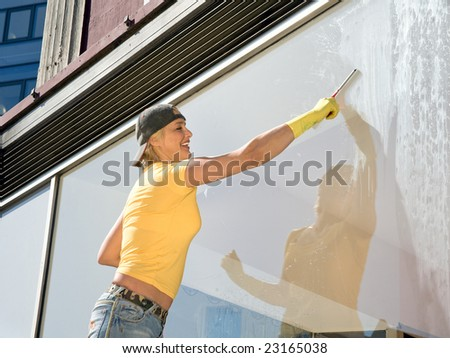 women in yellow T-shirt cleaning a window
