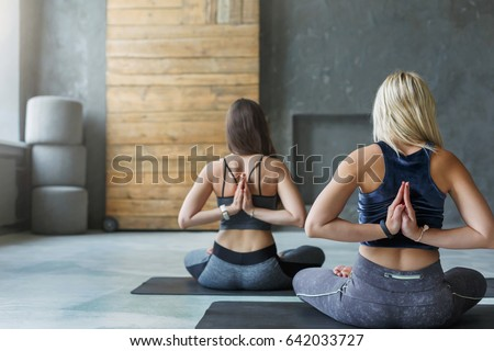 Women in yoga class making asana exercises. Girls do Reverse Prayer Pose, back and shoulders stretching. Healthy lifestyle in fitness club. #642033727