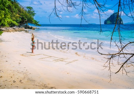 Women inscribed Help on the beach with waves and Rock in the background on a hot sunny day, El Nido, Palawan, Philippines. #590668751