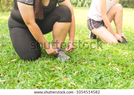 women joggers tying shoelaces. #1054514582