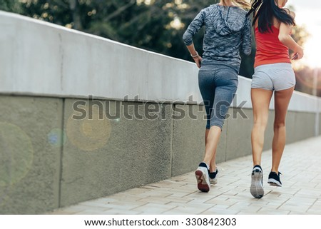 Women jogging in city in dusk and improving their stamina while losing weight