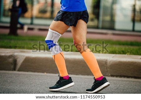 women legs runner in compression socks and kneepad
