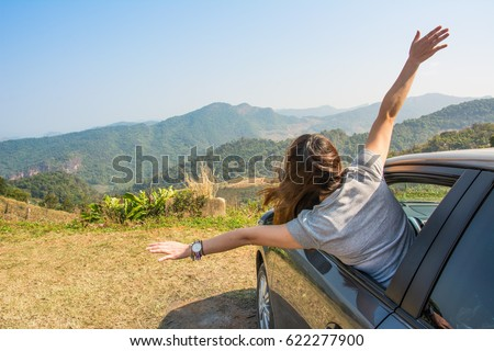 Women lifestyle enjoy with nature. woman relaxing and  raising arms out of window in a car road trip #622277900