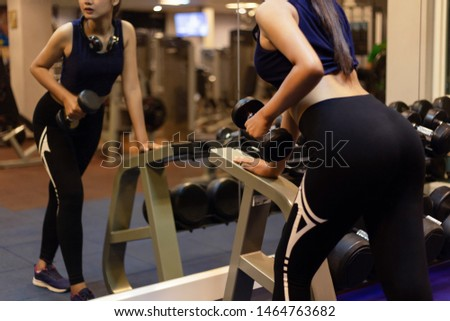 Women lift dumbbells workout in the evening. Fitness Club.