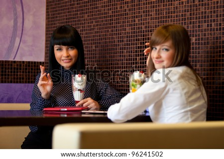 women look in camera and waving hands