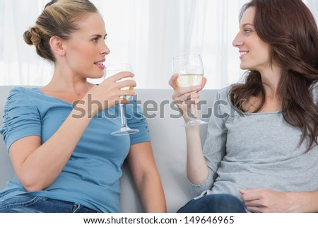 Women looking at each other clinking their wine glasses while sitting on the sofa
