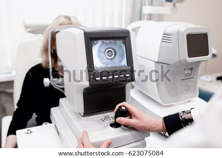 Women looking at eye test machine in ophthalmology clinic