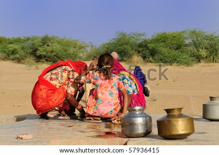 Women looking for the water in well on the desert. Rajasthan, India.
