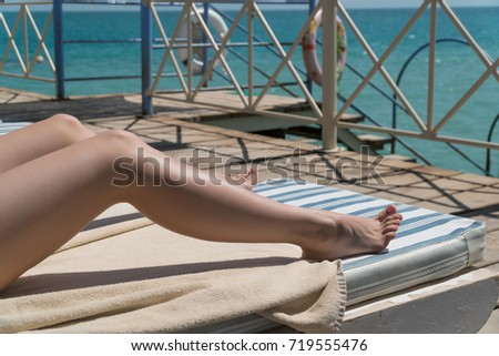 Women lower body lying with sunblock cream in shape for skin cancer sunburn care concept. #719555476