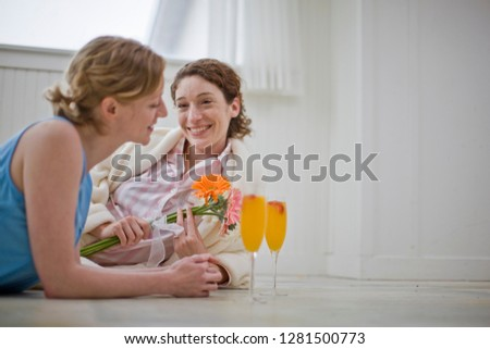 Women lying on floor in house with orange juice and flowers #1281500773