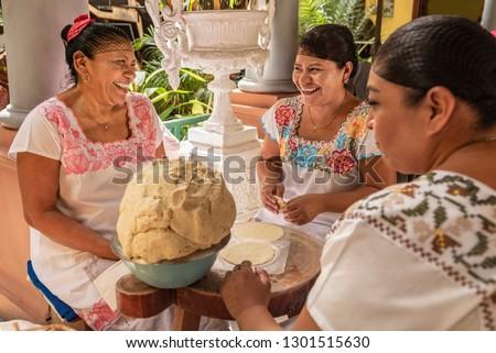 Women making Tortillas Group of smiling cooks preparing flat bread tortillas in Yucatan, Mexico #1301515630