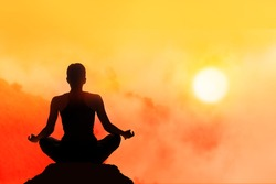women meditating on high mountain in sunset background